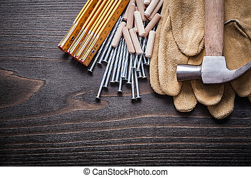 Wooden meter stack of dowels claw hammer brown safety gloves and