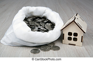 wooden miniature house with Russian ruble coins in the white bag