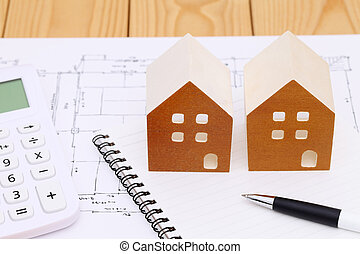 Wooden model of house and blueprints