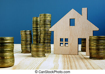Wooden model of house and money. Buy or sell property.