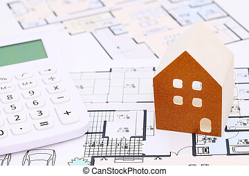 Wooden model of house on blueprints