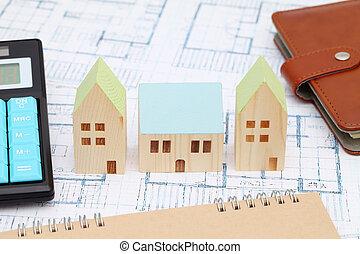Wooden model of house on blueprints