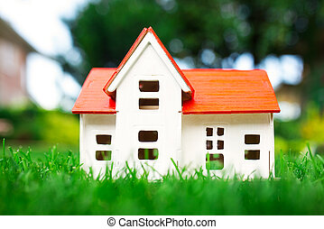Wooden model of house on grass, summer outdoor, new home concept