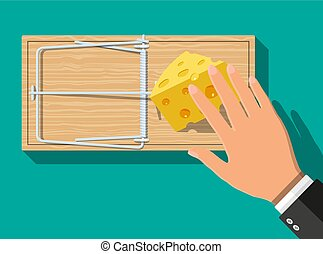 Wooden mouse trap with cheese and hand