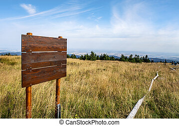Wooden multi sign on the top of a hill