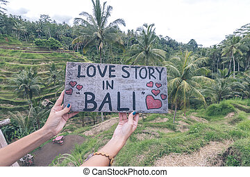 Wooden nameplate with text love story in Bali in the woman hands on a tropical rice terrace background of Bali island of parardise, Indonesia.