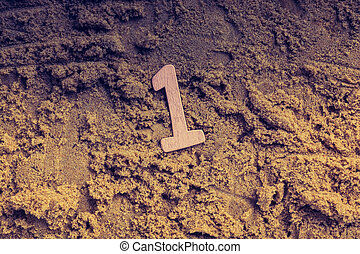 Wooden number 1 one on sand background