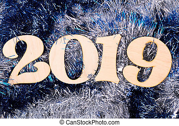 Wooden number 2019 on shiny tinsel background.