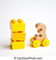 wooden numbers 0, 1, 2, 3, 4, 5 letters train cars alphabet with yellow wheels on white background. Early childhood education, learning to count, preschool and kids game concept
