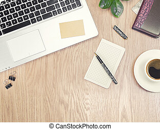 Wooden office desk table with laptop computer, green plant, pen, and a cup of black coffee. Top view with copy space, flat lay