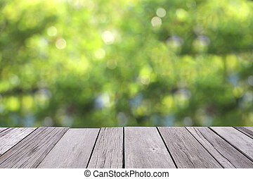 Wooden old plank with blurred greenery background.