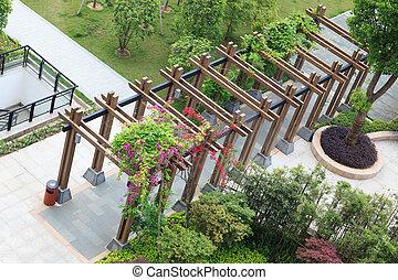 A small open wooden gazebo or pavilion in a garden