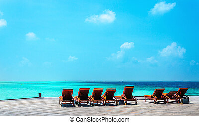 Wooden orange deck chairs on a pier on the background of the azure water