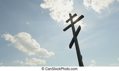 Wooden orthodox Cross in front of blue sky - Time Lapse