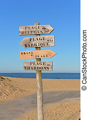 wooden panel in the sand indicating in french  : beluga beach,  Barrel Beach , Big beach and  chardon beache, names of of  Atlantic beaches in atlantic ocean in France