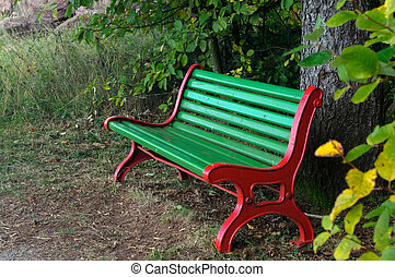 Wooden park bench under trees in the forest