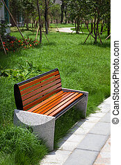 Wooden bench and alley in the garden.