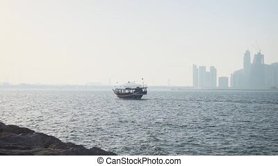 Wooden passenger dhow passes by a hazy view of the Doha, Qatar skyline, in the Persian Gulf. Video 4k Ultra HD