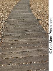 wooden path between pebbles