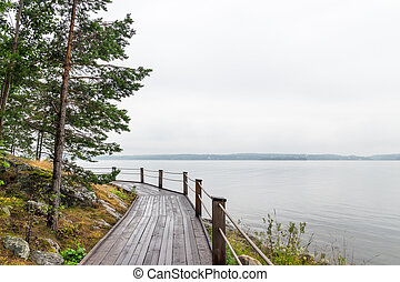 Wooden path going along the calm lake.