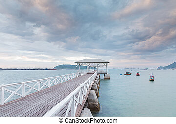 Wooden pavilion and walkway leading to ocean with beautiful sky background