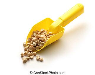 Wooden pellets on yellow shovel