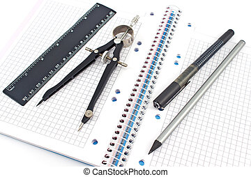 Wooden pencil, pen, drawing compass and ruler on spiral notebook