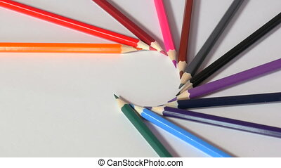 Wooden pencils form circle with their sharp ends, pencils are taken away one by one and then after all are gone put back together in same order, colours of rainbow. Close up,