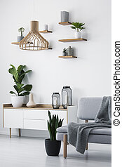 Wooden pendant light, simple shelves on a white wall and a plant on a scandinavian sideboard in a monochromatic living room interior