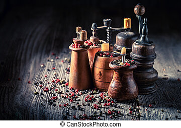 Wooden pepper mills with different types of pepper