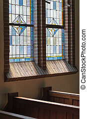 Wooden pews in an old Dutch church with a colorful stained glass window