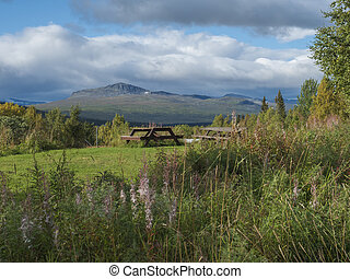 Wooden picninc tables with view onl andscape of Sarek mountains in Kvikkjokk in Swedish Lapland. Summer sunny day