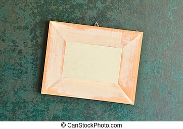 wooden picture frame on old green wall