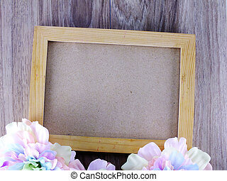 wooden picture frame on wooden background with flowers