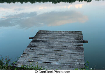 wooden pier and calm waters of the lake at dusk