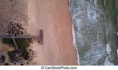 Wooden pier and waves in Quinta do Lago, Algarve, Portugal -...