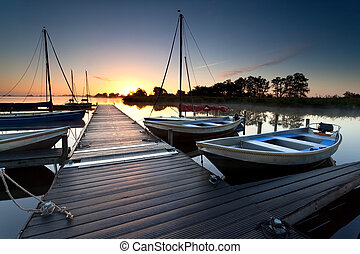 wooden pier and yachts on lake at sunrise