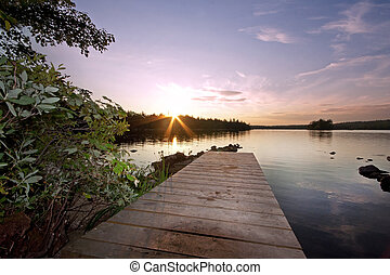 wooden pier at sunset by lake