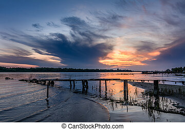 Wooden pier at sunset in the summer. Horizontal view of a wooden pier near a muddy shoreline over sunset sky on background
