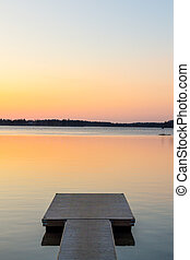 Wooden pier in the calm evening lake portrait