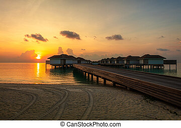 Wooden pier, jetty at tropical island resort in the evening sunset time, Maldives. Vacations And Tourism Concept