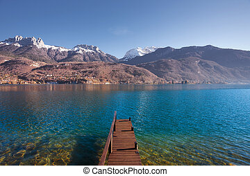 An old wooden pier faces the snow-capped mountains of the French alps on beautiful Lake Annecy. Horizontal
