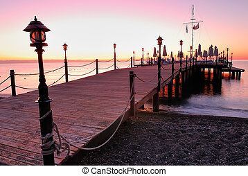 Wooden pier lighted by pink sunrise glow