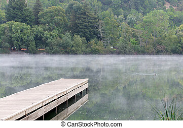 Wooden pier on a calm lake with fog