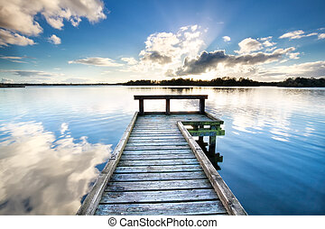 wooden pier on big lake and blue sky