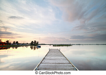 wooden pier on big lake at sunset