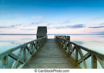 Wooden pier on calm lake at sunset