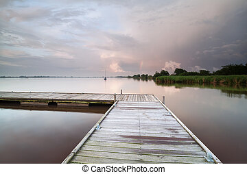 wooden pier on lake during shower at sunset