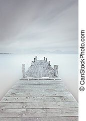 Wooden pier on lake in a cloudy and foggy mood. - Wooden...