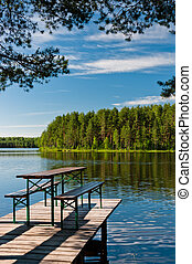 Wooden pier on lake with benches